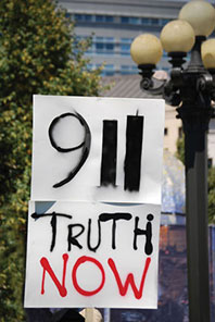 protestor's sign that reads '911 TRUTH NOW'