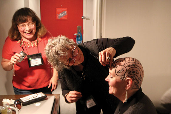 a women draws lines and writes words on Susan's head